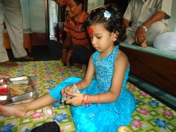 A little girl counting her Dakshina (the money given to the younger girls as a blessing along with tika). Usually the elder members give Dakshina to the daughters in the family.