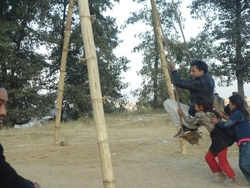 Young man swinging on a Linge ping. The swings like this are constructed at various empty fields and also in front of the temples during the festival of Dashain.